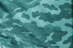 Old camouflage cloth in cyan tone. Abstract background and texture for design abd ideas stock image