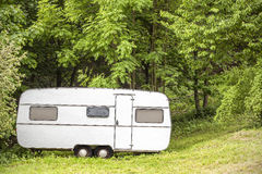 Old camping trailer standing in woods on summer day. Royalty Free Stock Photos
