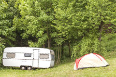 Old camping trailer and tent in the forest Stock Photos