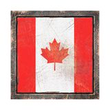Old Canada flag. 3d rendering of a Canada  flag over a rusty metallic plate in an old frame. Isolated on white background Royalty Free Stock Photos