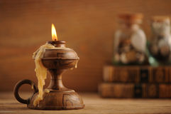 Old candle. On a wooden table, old books in the background stock image