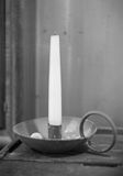 Old candle in a brass candlestick on a table royalty free stock photography