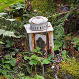 Old candle lamp embedded in garden. Ornamental storm lamp for candle in summer garden Royalty Free Stock Photos