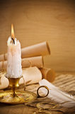 Old Candle On Table With Rolls Of Paper Stock Images