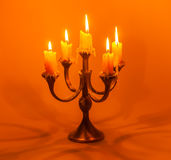 Old candlestick with candles. Old candlestick with burning candles on a red background royalty free stock images