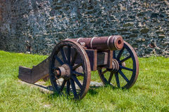 Old cannon. Old artillery in the medieval castle. Green grass and stone wall in the background Royalty Free Stock Photos