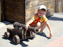 The old cannon. The child sits next to an old cannon arms around her Royalty Free Stock Photos