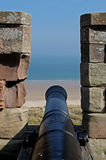 Old Cannon looking over beach, Northumberland. Stock Image