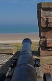 Old Cannon looking over beach, Northumberland. Royalty Free Stock Image