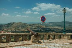 Old cannon overlooking hilly landscape in Monsanto. Old iron cannon over stone parapet and NO PARKING road sign, overlooking hilly landscape in a sunny day at stock photo
