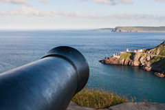 Old Cannon pointing at Seaside Town Stock Image