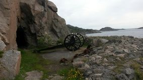 Old Cannon by the Sea. An old cannon that points out to the fjord, with a cave in the background Stock Photos