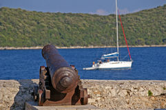 Old cannon at seaside with blue water. And small turistic boat Stock Photography