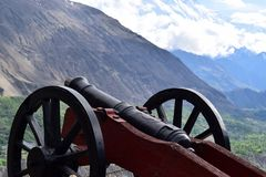 An old cannon stands on fort. In the background is a mountain royalty free stock photography
