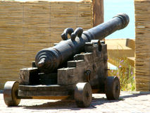 The old cannon. Old cannon on a wooden frame basking in the sun Stock Image