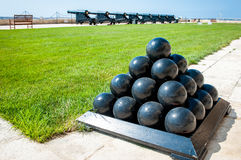 Old cannonballs stacked in pyramid, in front of cannons, on Valletta Castle, Malta Royalty Free Stock Photos