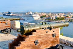 Old cannons facing the city of Havana with an modern cruise ship. On the bay stock photography