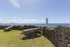 Old cannons and lighthouse at Vieux-Fort Stock Photos