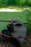 Old canoe ashore the pond with bucket on it Stock Photography
