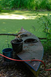 Old canoe ashore the pond with bucket on it Royalty Free Stock Photo