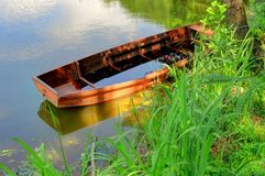 Old Canoe in a lake. A red orange wooden boat sits on a lake, filling with water Stock Photos