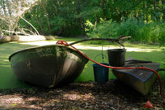 Old canoe and a wooden boat ashore the pond with bucket on it Royalty Free Stock Photos