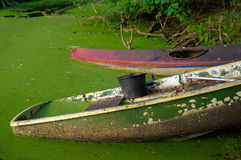 Old canoe and a wooden boot ashore the pond with bucket on it Royalty Free Stock Photography