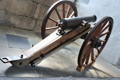 An ancient canon. An old canon with wheels, in a castle royalty free stock images