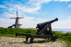 Old Canon with Windmill Background Stock Photo