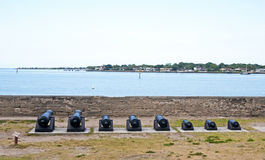 Old canons lined up in front of the bay aiming at the sea. Royalty Free Stock Image