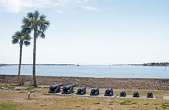 Old canons lined up in front of the bay aiming at the sea. Stock Photo