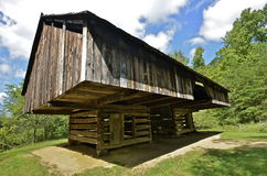 Old cantilevered weathered barn. A very old cantilevered weathered barn rests on two square log bases which serve as pens Stock Image