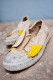 Old canvas shoes. The Old canvas shoes patched by tape royalty free stock photo