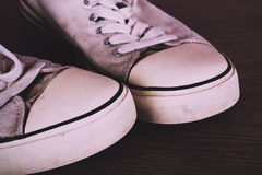 Old canvas shoes on a wooden floor Vintage Retro Filter. Stock Photo
