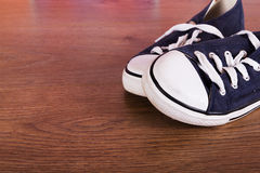 Old canvas shoes on a wooden floor Royalty Free Stock Image
