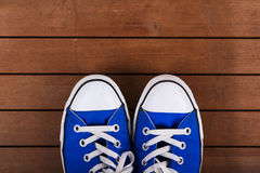 Old canvas shoes on a wooden floor Stock Photos