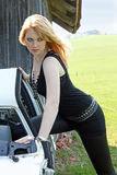 The old car. A young blond woman by an old scrap metal carriage Stock Photos