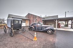 Old car and Amish buggy. Old rusty car and Amish buggy at an old store in Dublin, Pa. USA. Jan. 22, 2017 Royalty Free Stock Images