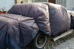 Old car covered with a rain tent.  royalty free stock images