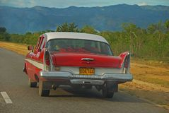An old car cruising on Cuban country side with a view of the road, mountain and forest in the background Royalty Free Stock Photography
