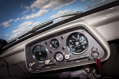 Old Car Dashboard. Retro British Auto Interior. Detail with Blue Sky and Clouds royalty free stock photo