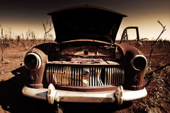 Old Car in Desert. An old car lay abandoned in the heart of a baron landscape Royalty Free Stock Image