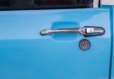 Old car door handle on blue car Stock Photo