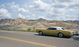 Old car driving in Badlands National Park Stock Photos
