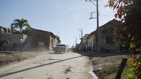 Old car on dust country road in colonial city stock video footage