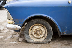 Old car with flat tire. Royalty Free Stock Photo