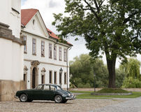 Old car in front of a mansion Stock Photo