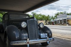 Old car with the general store and post office on the background in the small town of Hye in Texas, USA Stock Photos