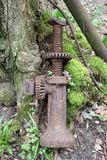 Old car jack by tree. Old car jack leaning on the base of a moss covered tree with other metal objects in the background Royalty Free Stock Photo