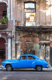 Old car next to decaying buildings in Havana Stock Images